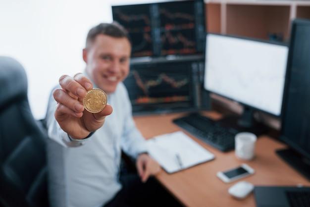 Geschäftsmann, der bitcoin in der hand hält, während er im modernen büro mit vielen monitoren mit graphen sitzt.