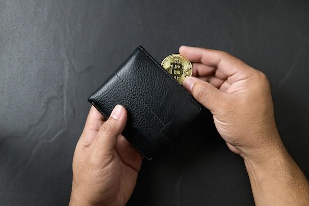 Geschäftsmann, der bitcoin in eine schwarze lederbrieftasche auf schwarzem hintergrund setzt. bitcoin-konzept speichern.