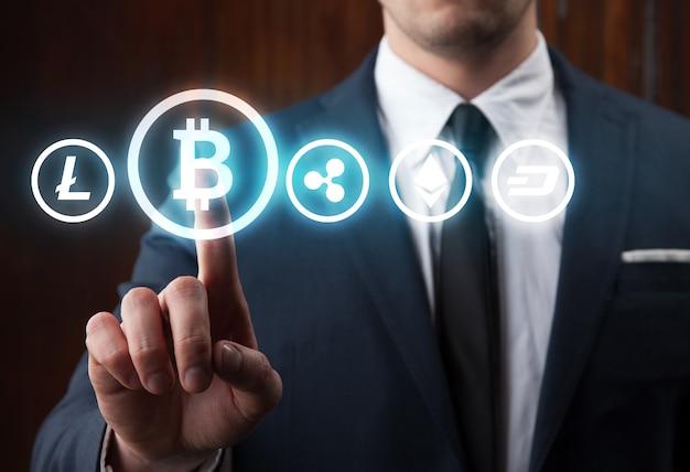 Geschäftsmann, der bitcoin-symbol drückt, das von anderer kryptowährung auf schwarzem hintergrund wählt.