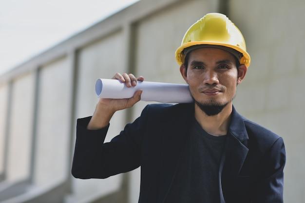 Geschäftsmann, der blaupausengebäude-bau hält