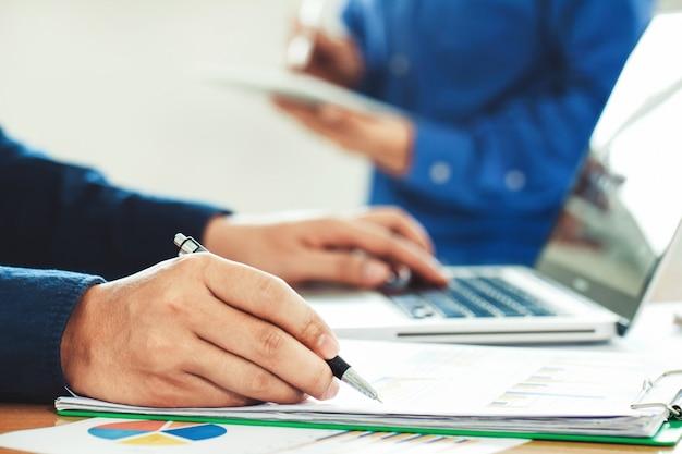 Geschäftsmann, der börsenbericht und finanzarmaturenbrett mit handelsnachrichten, mit schlüsselleistungsindikatoren analysiert. unternehmerteam, das im kreativen büro arbeitet