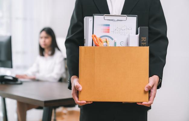 Geschäftsmann, der braunen karton mit dokumenten und persönlichem büro verpackt und hält