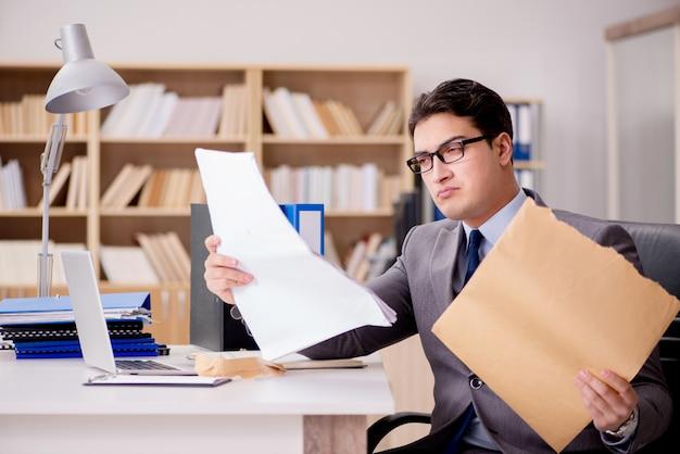 Geschäftsmann, der briefumschlag im büro empfängt