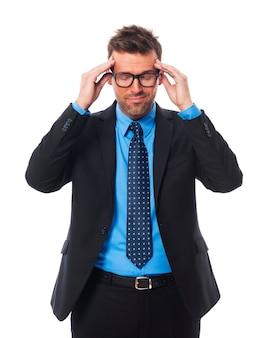 Geschäftsmann, der brille mit schrecklichen kopfschmerzen trägt