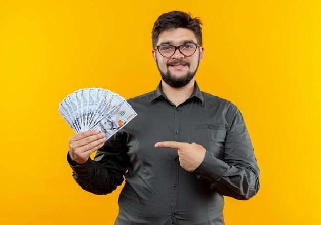 Geschäftsmann, der brillen hält und punkte auf bargeld lokalisiert auf gelb trägt