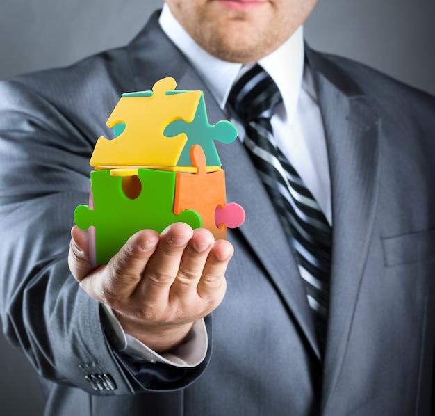 Geschäftsmann, der buntes puzzlespielhaus handhabt
