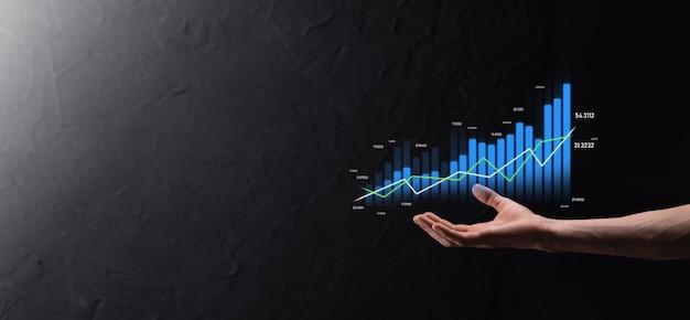 Geschäftsmann, der das diagrammwachstum und die zunahme der positiven diagrammindikatoren in seinem geschäft hält