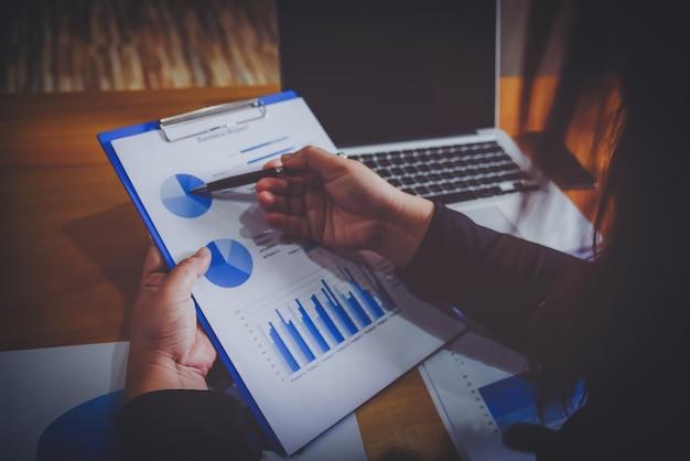 Geschäftsmann, der das investitionsdiagramm arbeitet im büro hält und analysiert. geschäftsarbeitskonzept.