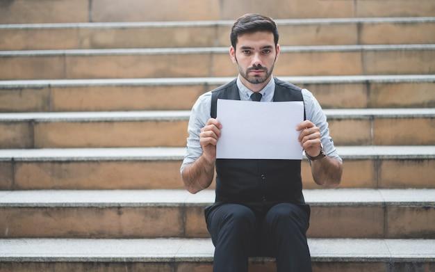 Geschäftsmann, der das leere weißbuch sitzt auf der treppe hält