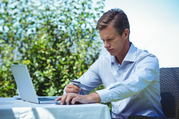Geschäftsmann, der das on-line-einkaufen mit laptop und kreditkarte tut