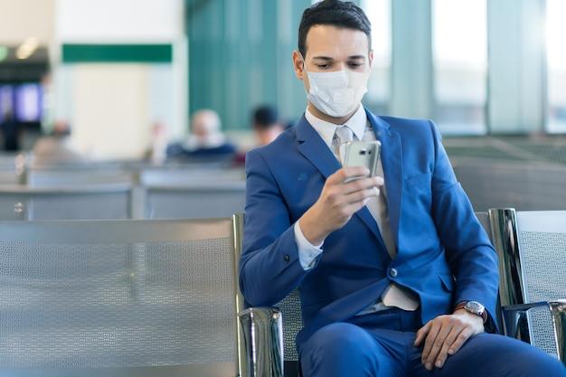 Geschäftsmann, der das telefon am flughafen nutzt, covid- oder coronavirus-konzept