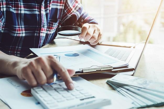 Geschäftsmann, der das vergrößern verwendet, um die bilanz jährlich mit der anwendung des taschenrechners und der laptop-computers zu wiederholen