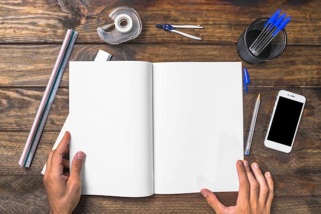 Geschäftsmann, der das weißbuch umgeben mit schreibwaren und mobiltelefon hält