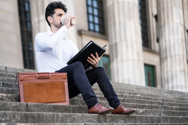 Geschäftsmann, der dateien liest und eine tasse kaffee trinkt, während er draußen auf treppen sitzt. unternehmenskonzept.