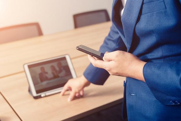 Geschäftsmann, der daten mit smartphone zwischen dem treffen des unternehmenserfolgbrainstormings serching ist