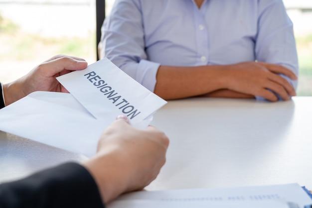 Geschäftsmann, der dem ausführenden arbeitgeber ein kündigungsschreiben übergibt