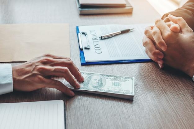 Geschäftsmann, der dem geschäftsführer dollarschein-korruptionsbestechung gibt, um vertrag zu behandeln