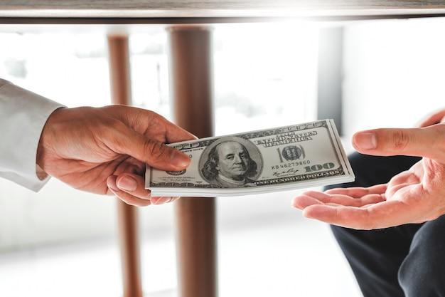 , geschäftsmann, der dem geschäftsführer dollarscheine gibt, um vertrag zu beschäftigen