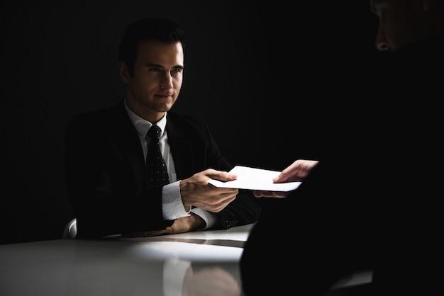 Geschäftsmann, der dem partner bestechungsgeld im umschlag gibt