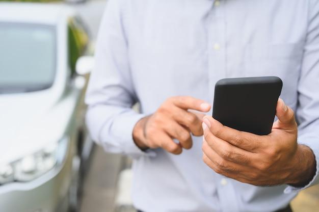 Geschäftsmann, der den smartphone steht nahen autohintergrund verwendet. der mann, der intelligenten telefonanruf um hilfe verwendet, gliederte auto auf dem straßenkonzept auf.