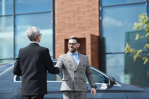 Geschäftsmann, der der geschäftsfrau die hand schüttelt, während sie sich in der nähe des bürogebäudes treffen