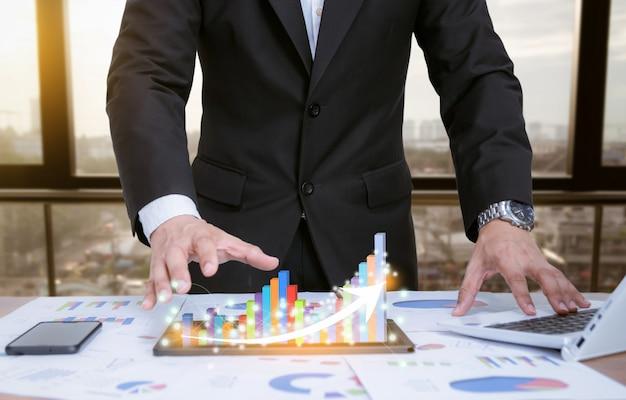Geschäftsmann, der diagramme mit technologischen geräten analysiert