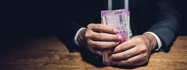 Geschäftsmann, der die geldbanknoten der indischen rupie in der dunkelkammer hält
