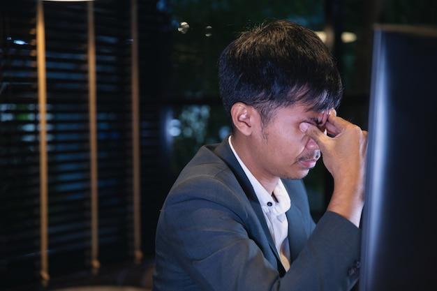 Geschäftsmann, der die gläser ermüdet von der computerarbeit, augenmüdigkeitskonzept nimmt