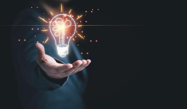 Geschäftsmann, der die hälfte der virtuellen glühbirne und des gehirns auf blauem bokeh-hintergrund hält, intelligente denkidee und inspirationsinnovationskonzept.