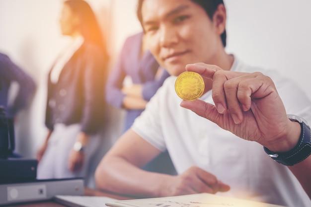 Geschäftsmann, der die kryptowährungsmünze der waage vor kurzem eingeführt zur weltwirtschaft des digitalen geldes hält
