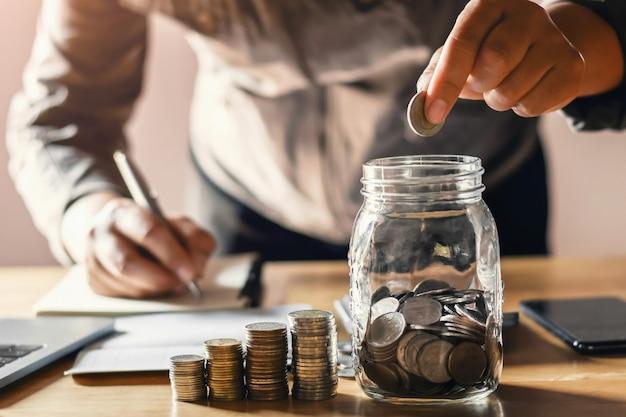 Geschäftsmann, der die münzen sich setzen in glas hält. konzept geld sparen und finanzbuchhaltung