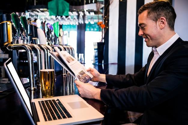 Geschäftsmann, der die nachrichten liest und laptop am zähler in einer stange verwendet