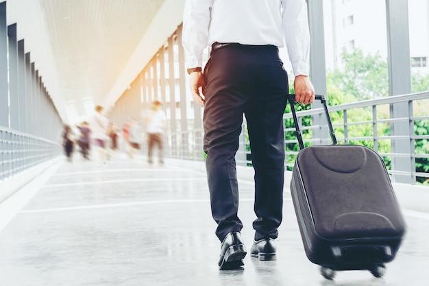 Geschäftsmann, der die rollentasche hochgeht auf reise hält