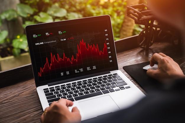 Geschäftsmann, der die täglichen handelspreise an der online-börse durch laptop zu hause betrachtet.