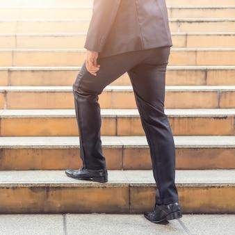 Geschäftsmann, der die treppe hinaufgeht