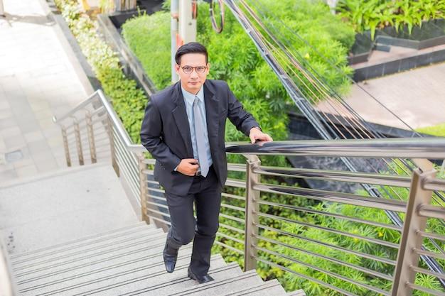 Geschäftsmann, der die treppe in einer hauptverkehrszeit hinaufgeht, um zu arbeiten. beeil dich mal