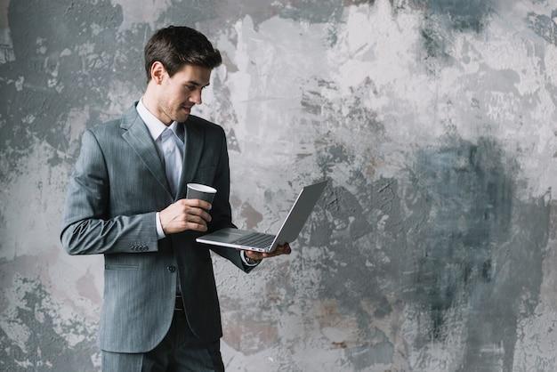 Geschäftsmann, der die wegwerfkaffeetasse betrachtet laptop hält