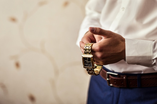 Geschäftsmann, der die zeit auf seiner armbanduhr überprüft, mann, der uhr auf hand hält, bräutigam, der am morgen vor der hochzeitszeremonie fertig wird