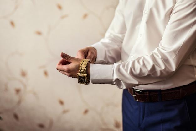 Geschäftsmann, der die zeit auf seiner armbanduhr überprüft, mann, der uhr auf hand hält, bräutigam, der sich am morgen vor der hochzeitszeremonie fertig macht