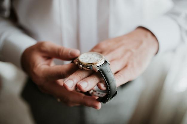 Geschäftsmann, der die zeit auf seiner armbanduhr überprüft