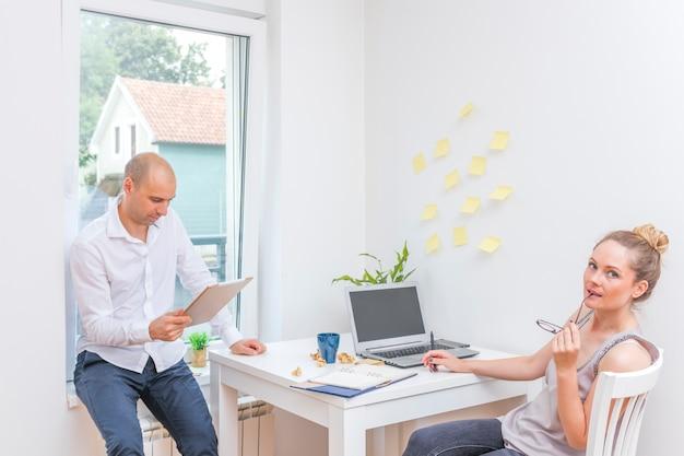 Geschäftsmann, der digitale tablette nahe seinem partner sitzt auf stuhl betrachtet
