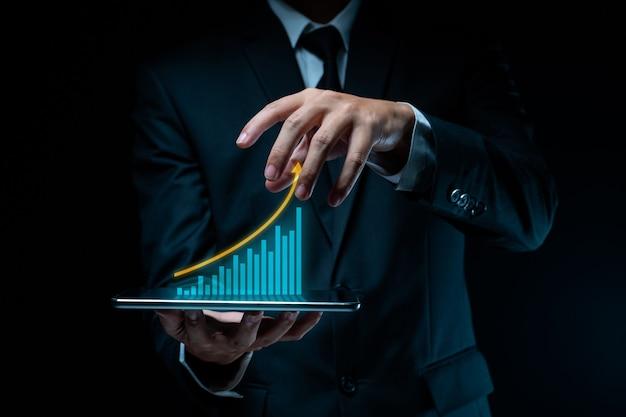 Geschäftsmann, der digitales marketing der tablettplanung mit diagrammhologrammeffekt verwendet