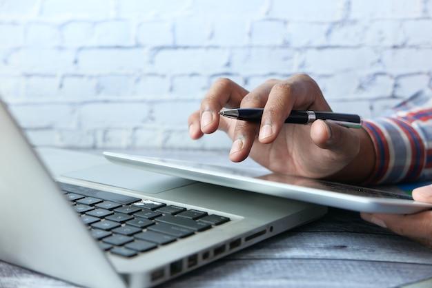 Geschäftsmann, der digitales tablett auf schreibtisch verwendet
