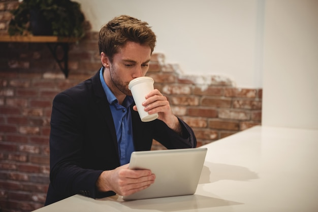 Geschäftsmann, der digitales tablett beim kaffee verwendet