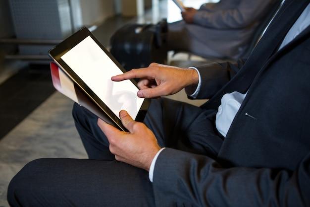 Geschäftsmann, der digitales tablett beim sitzen am flughafenterminal verwendet