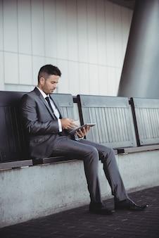 Geschäftsmann, der digitales tablett beim sitzen auf einer bank verwendet