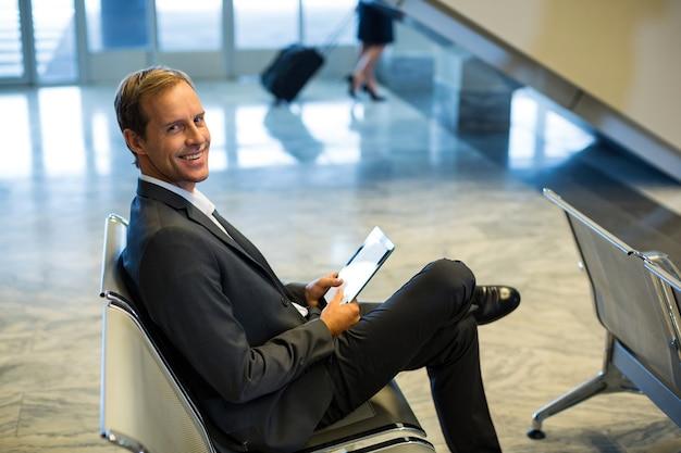 Geschäftsmann, der digitales tablett im wartebereich am flughafenterminal verwendet