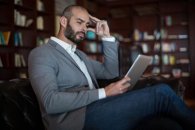 Geschäftsmann, der digitales tablett im wartebereich verwendet