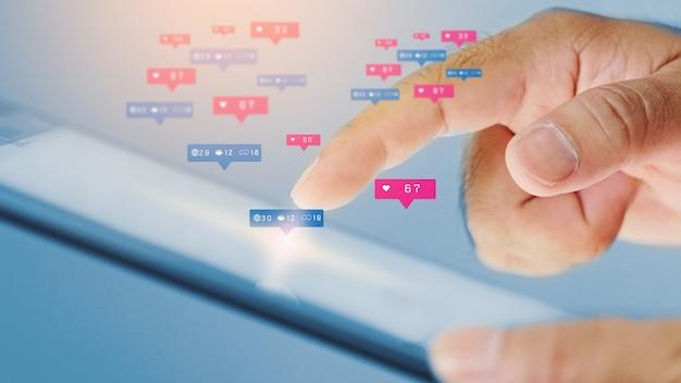 Geschäftsmann, der digitales tablett mit sozialen symbolen auf dem bildschirm verwendet