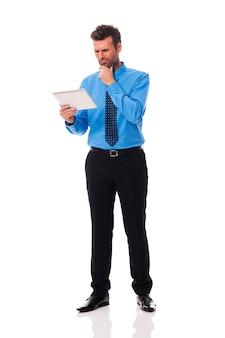 Geschäftsmann, der digitales tablett und grimassen hält